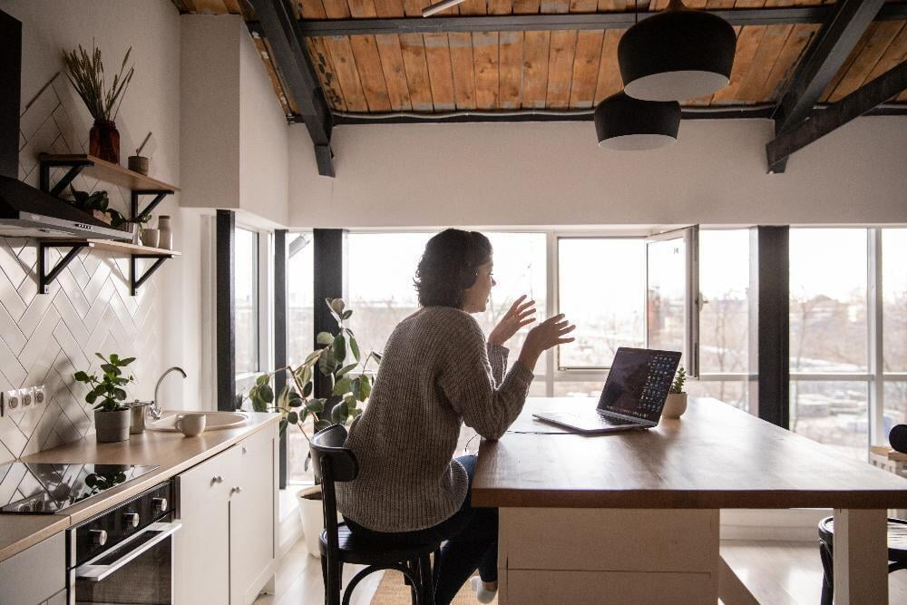 Woman Working on Laptop in the Kitchen